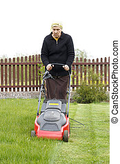 old woman mowing grass with an electric mower