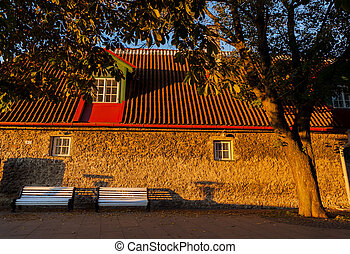 tallinn in golden light - Two benches in front of an old...