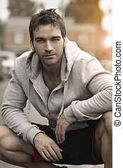 Male model - Very good looking man crouched down outdoors...