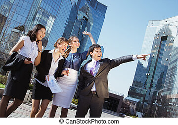 Happy diverse group of executives pointing over business...