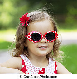 Little girl in fashionable sunglasses - The image of a...