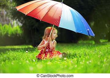 Little girl with a rainbow umbrella in park - The image of a...