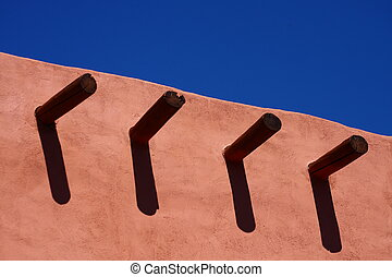 Timbers in Adobe Wall Under Blue Sky - An adobe wall with...