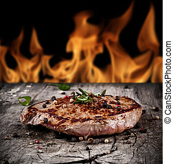 Delicious beef steak on wood with flames on background