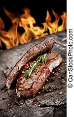 Delicious beef steaks on wood with flames on background
