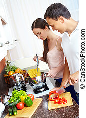 Cooking pasta - Portrait of amorous couple cooking pasta in...