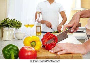 Cutting pepper - Close-up of young female cutting red pepper...