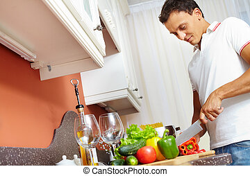 Man cooking - Portrait of young man cutting vegetables in...