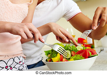Mixing salad ingredients - Close-up of human hands with...