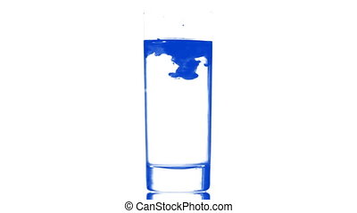 blue ink in glass of water