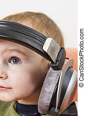 young child on couch with headphone