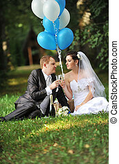 newly-married couple with balloons on green grass in field