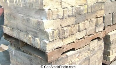 Plastic Wrap Around Brick on Pallet - Worker unrolls plastic...