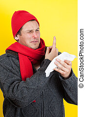 Man picking nose - Ill young man with red nose, scarf and...