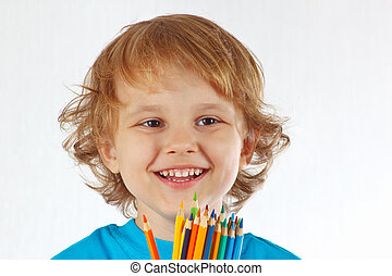 Little smiling boy with color pencils on a white background