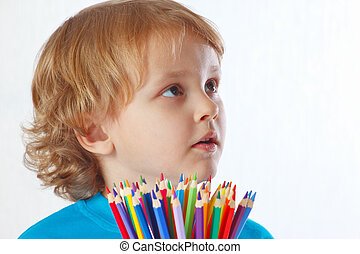 Young blond boy with color pencils on a white background