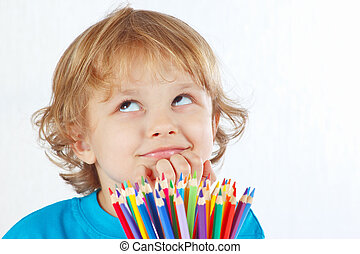 Young cute blond boy with color pencils on a white...