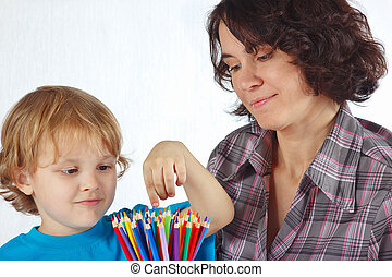 Little cute boy with his mother with color pencils on a...