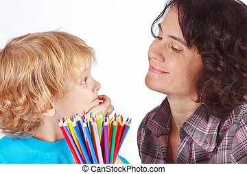 Little blond boy with his mother with color pencils on a...