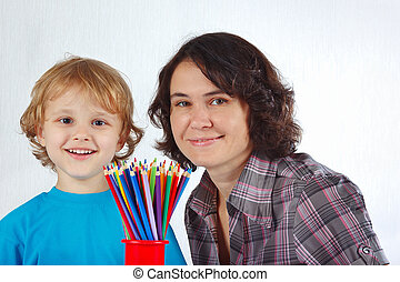 Young smiling boy with his mother with color pencils on a...