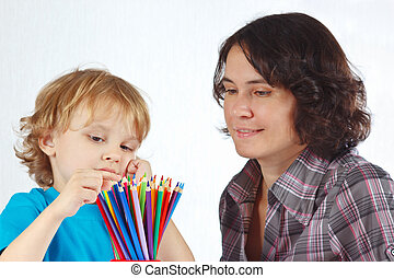 Little boy with young mother looks on color pencils on a...