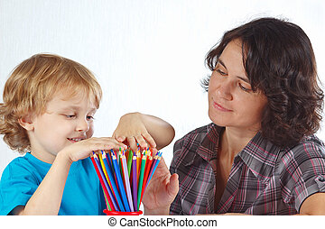 Little blond boy with his mother looks on color pencils on a...