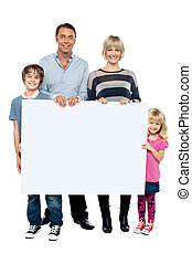 Active young family displaying blank ad board - Active young...