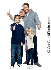Adorable family in winter clothes gesturing thumbs up Full...