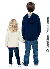 Rear view of two little kids. Boy holding his sister. - Rear...