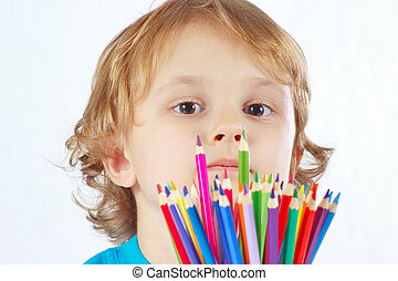 Little cute boy with color pencils on a white background