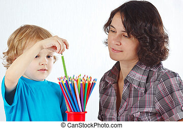 Little boy with young mother with color pencils on a white...