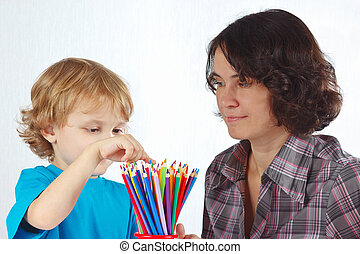 Little cute boy with his mother looks on color pencils on a...