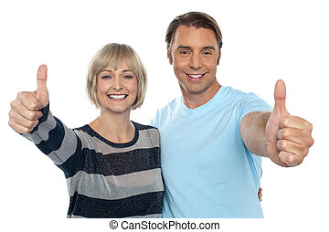 Confident couple showing thumbs up sign to the camera,...