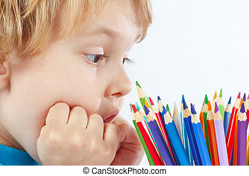 Little cute blond boy with color pencils on a white...