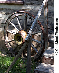 Spare Wheel - Old wagon wheel resting in front of pioneer...
