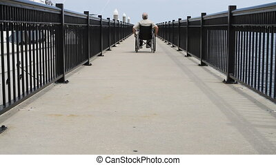 Man Rolling Away In Wheelchair - Man with his back to the...