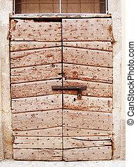Odd door made of diferent pieces of wood