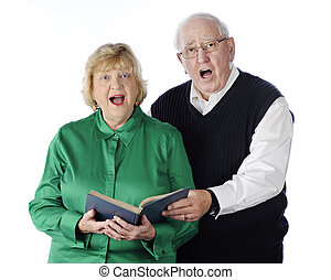 Singing Senior Couple - A senior adult couple singing...