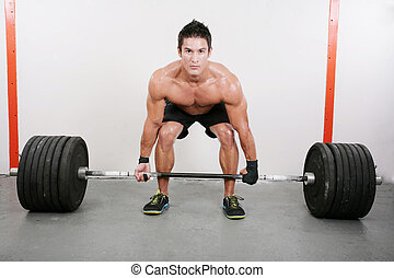 Young and muscular guy holding a barbell. Crossfit dead lift...