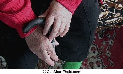 Old hands holding a stick