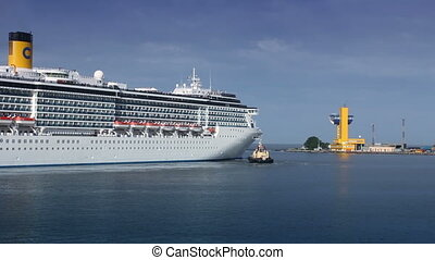A luxury cruise ship leaving port with tugs assistance