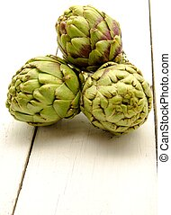 Artichokes - Fresh artichokes on white wooden table