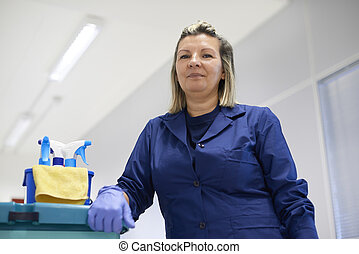 Portrait of happy professional female cleaner smiling in...