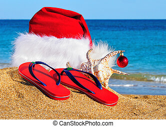 Santa Claus hat and slippers on the seashore against blue...