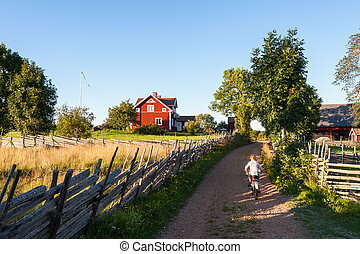 Child riding a bike in rural Sweden - Child riding a bicycle...