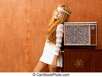 Blond vintage 70s kid girl with retro wood tv on wallpaper