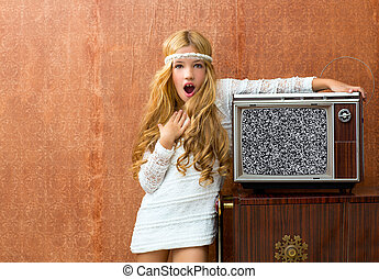 Blond vintage 70s kid girl with retro wood tv surprised...