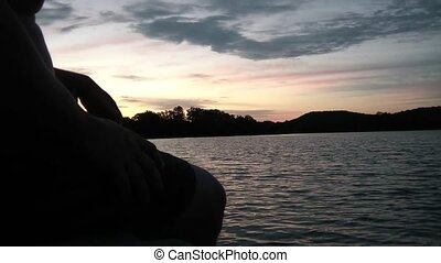 Guy Sitting on Bench Watching Sunrise over Lake - Lifestyle...
