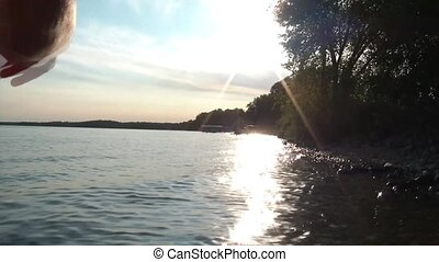 Skipping Rocks on Lake at Sunset - Arm is skipping rocks on...