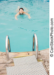 Swimming woman in an outdoor pool focus on foreground